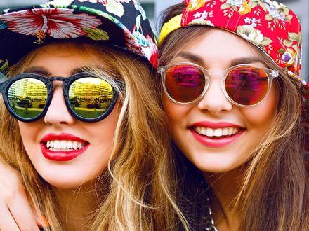 Фото Две улыбающиеся девушки в цветастых шапочках и темных очках, в стеклах которых отражаются здания курорта