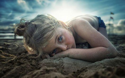Фото Сероглазая белокурая девочка лежит на песчаном морском берегу, положив руку под голову, фотограф John Wilhelm