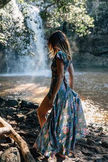 Фото Девушка в длинном цветном платье стоит на берегу реки