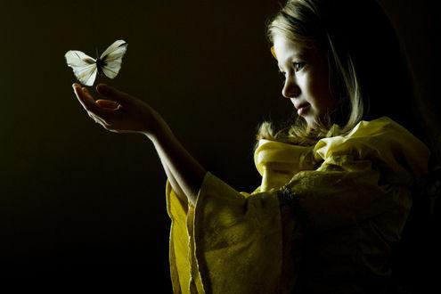 Фото Девочка в желтом платье в темноте ловит бабочку