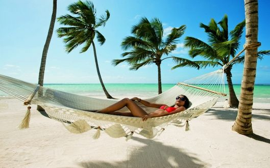 Фото Девушка отдыхает в гамаке на берегу моря