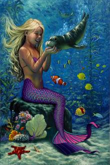Фото Девочка-русалка со светлыми длинными волосами сидит на камне на дне моря и трогает руками морского котика, кругом плавают разноцветные рыбки