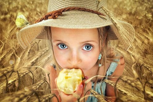 Фото Девочка в соломенной шляпке, стоя среди колосьев пшеницы, смотрит на нас большими глазами и ест яблоко, фотограф John Wilhelm