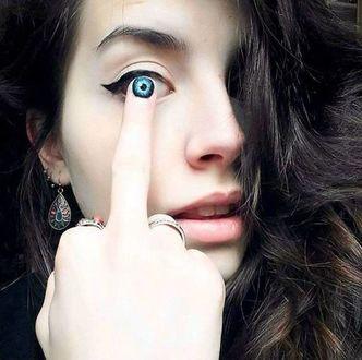 Фото Девушка с каштановыми волосами, с бижутерией на пальцах и ушах, держащая средний палец руки у глаза, на котором изображен глаз синего цвета