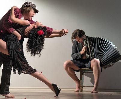Фото Мужчина сидит на табуретке и играет на баяне, другой мужчина и девушка под эту музыку танцуют танго, автор Andrey Razoomovsky / Андрей Разумовский