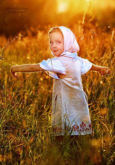 Фото Девочка в белом платье, с травинкой в губах стоит, раскинув руки в лучах солнца, фотограф Наталья Законова