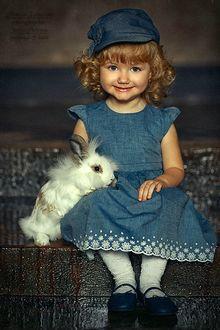 Фото Девочка с кудрявыми светлыми волосами в джинсовой кепочке и сарафане сидит на ступеньках с белым кроликом, фотограф Наталья Законова