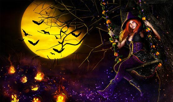 Фото Девушка с длинными рыжими волосами в шляпе-колпаке сидит на качели на фоне тыкв и луны с летучими мышами