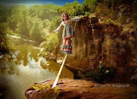 Фото В солнечный день, девочка идет по канату через обрыв