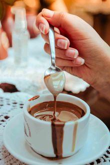 Фото Девушка держит в руке ложку над чашкой с десертом