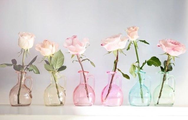 Фото Розочки стоят в разноцветных, стеклянных кувшинчиках