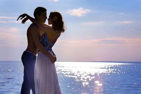 Фото Влюбленная пара на фоне красиво освещенного моря и розово-голубых облаков