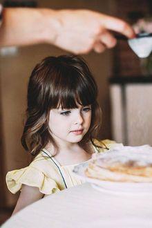 Фото Маленькая темноволосая девочка смотрит как мама посыпает пудрой блинчики