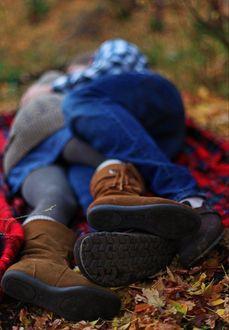 Фото Влюбленные лежат на пледе среди осенней листвы