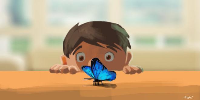 Фото Маленький мальчик смотрит на голубую бабочку