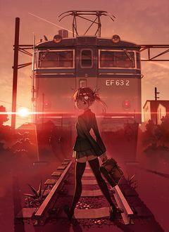 Фото Девушка с портфелем стоит на железнодорожных путях перед поездом