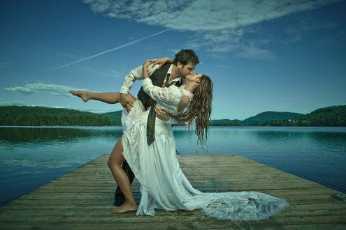 Фото Парень целует свою возлюбленную, пара стоит на мостике, фотограф Ned Mansour