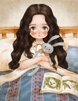 Фото Девочка в кровате обнимает игрушечного кролика, рядом лежит книга