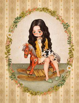 Фото Девочка с котенком сидит на игрушечной лошадке
