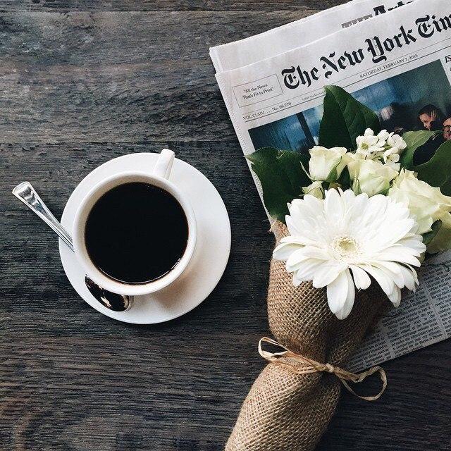 Фото Кружка кофе, букет цветов и газета на столе