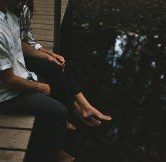 Фото Парень с девушкой сидят на мосту, свесив ножки