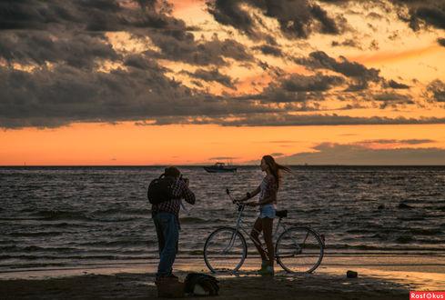 Фото Мужчина фотографирует девушку с велосипедом на фоне моря