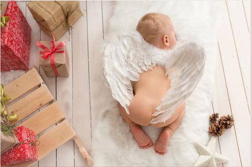 Фото Ребенок с крыльями ангела на белом коврике, среди коробок с подарками, фотограф Анастасия Нагорная