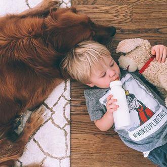 Фото Мальчик пьет из бутылки, лежа на полу и обнимая игрушку, рядом лежит собака