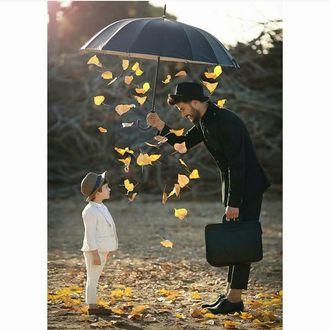 Фото Парень держит зонт, из которого падают осенние листья, над мальчиком