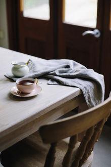 Фото Чашка с кофе, полотенце и кувшинчик стоят на столе