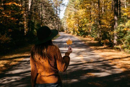 Фото Девушка в шляпе с кленовым листом в руке стоит на дороге, фотограф Gabriela Tulian