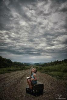 Фото Девочка сидит на чемоданах посреди дороги