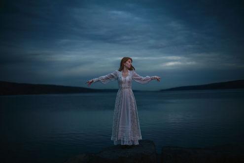 Фото Девушка в длинном платье стоит на камне на фоне водоема