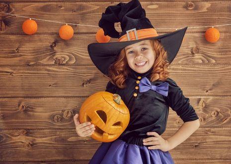 Фото Девочка в шляпе ведьмы стоит с тыквой-фонарем в руке