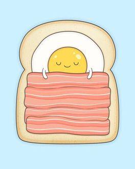 Фото Жареное яйцо лежит на куске хлеба, прикрывшись беконом