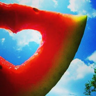 Фото В кусочке арбуза прорезано отверстие в форме сердечка