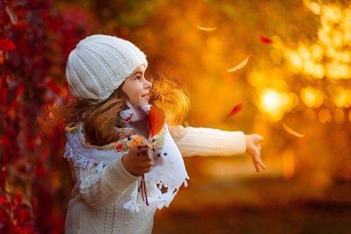 Фото Девочка стоит под листопадом