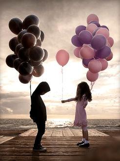 Фото Мальчик и девочка стоят друг напротив друга с воздушными шарами