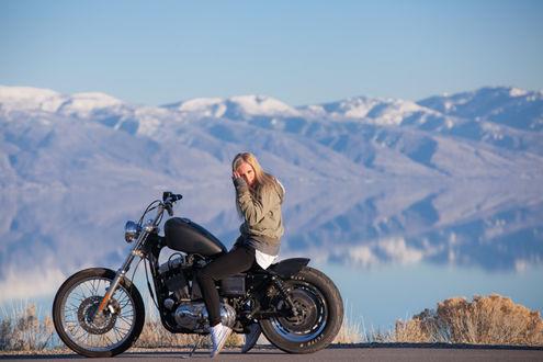 Фото Девушка сидит на мотоцикле на фоне гор