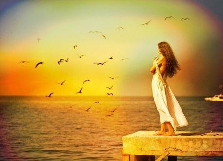 Фото Девушка стоит на пирсе у моря