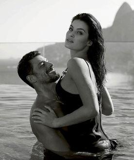 Фото Парень держит девушку на руках, оба стоят в воде