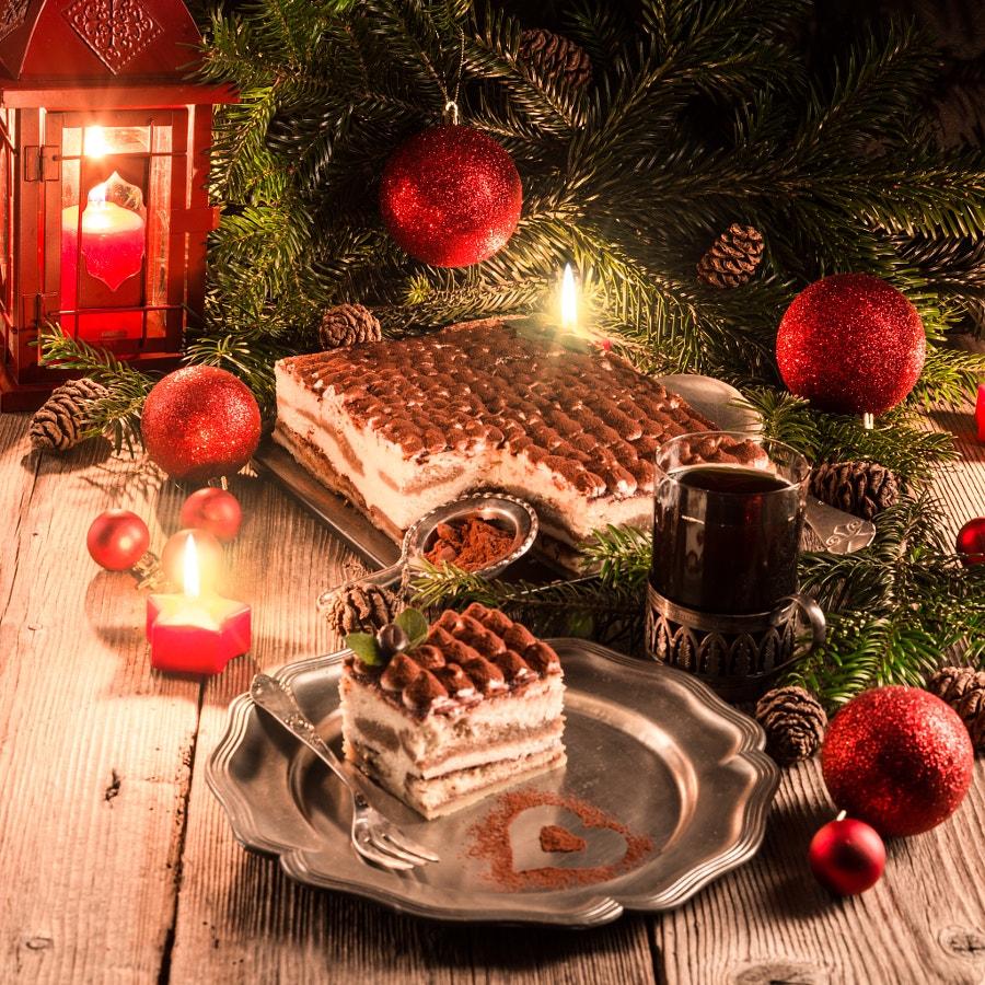 Тирамису к Рождеству, напиток в стеклянном стакане, новогодние шарики, горящая свеча, елочные ветви с шишками и фонарь, фотограф Darius Dzinnik
