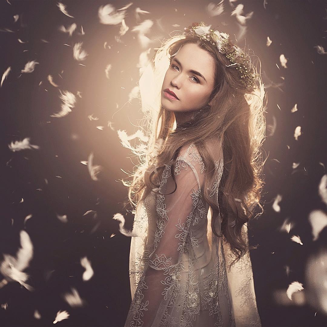 Фото Красивая девушка грустная с венком из цветов в полупрозрачном платье на фоне летающих перьев