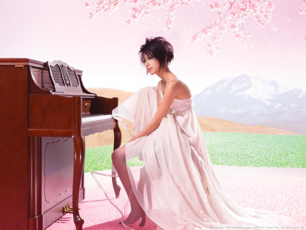 Фото Mika Nakashima / Мика Накасима в полупрозрачном нежно- розовом длинном платье сидит на банкетке у пианино на фоне горного пейзажа