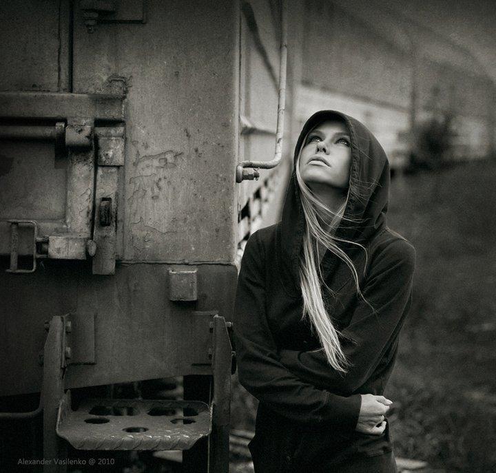 Фото Девушка блондинка в толстовке с капюшоном смотрит вверх, стоя у последнего вогона старого поезда, by Alexander Vasilenko