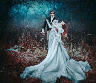 Фото Парень поддерживает рукой девушку в длинном белом платье, стоя в лесу под снегопадом, фотограф Светлана Беляева