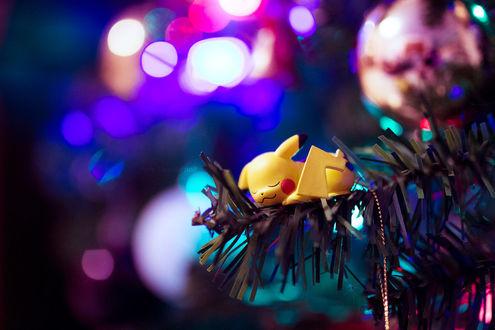 Фото Игрушка в виде Pikachu / Пикачу, персонажа из аниме Pokemon / Покемон лежит на еловой ветке на фоне бликов