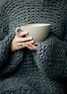 Фото Руки девушки в связанном свитере держат большую белую чашку