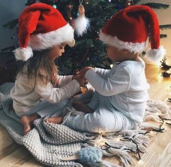 Фото Маленькие дети, с новогодними колпаками на голове, сидят у елки