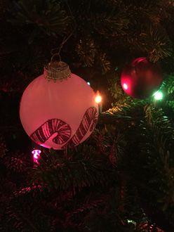 Фото Розовый новогодний шар и гирлянда на елке